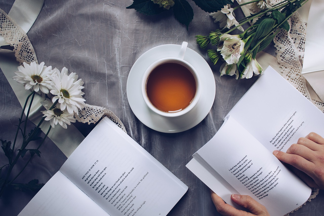 two books of poetry open with flowers on the desk and a cup of coffee